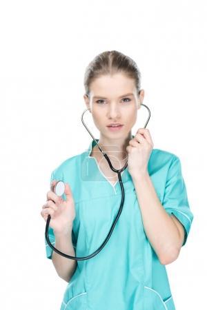 Foto de Enfermera joven usando estetoscopio y mirando a la cámara aislada en blanco - Imagen libre de derechos