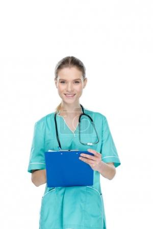 Photo for Young nurse writing at clipboard and looking at camera isolated on white - Royalty Free Image