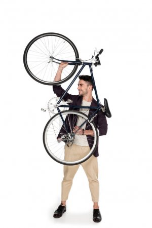 Photo for Smiling stylish young man holding bicycle and looking away - Royalty Free Image