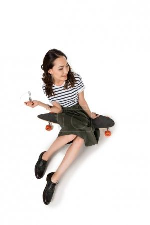 Photo for High angle view of smiling hipster girl sitting on skateboard and looking away - Royalty Free Image