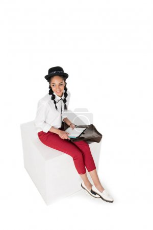 Photo for Smiling young woman sitting with leather bag on knee and using digital tablet with blank screen - Royalty Free Image
