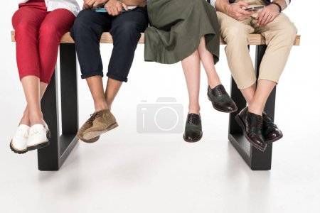 Photo for Cropped shot of young friends using digital devices while sitting together on bench - Royalty Free Image