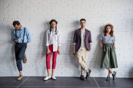 Photo pour Jeunes amis multiethniques posant dans des vêtements élégants près du mur de briques - image libre de droit