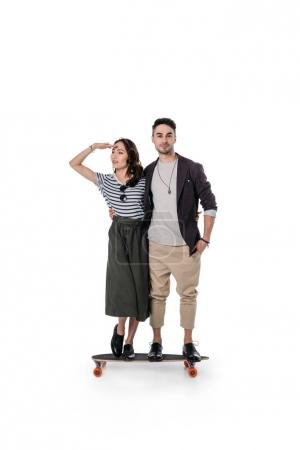 young casual couple standing on skateboard