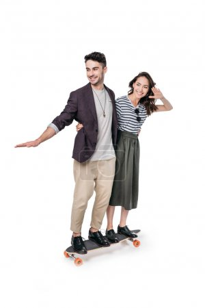 Photo for Young stylish couple riding on skateboard isolated on white - Royalty Free Image