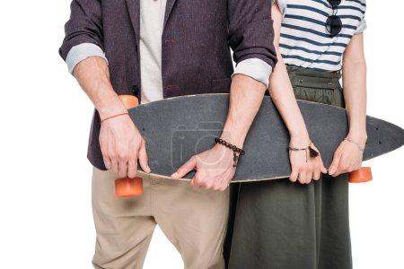 Casual couple holding skateboard