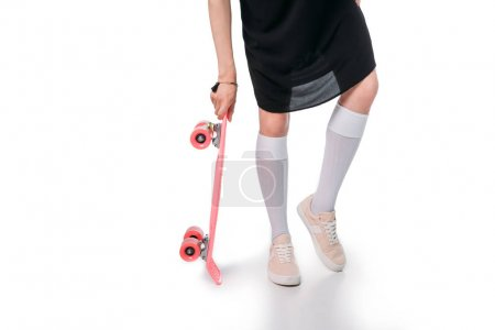 Casual woman holding skateboard