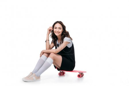 smiling asian girl sitting on skateboard