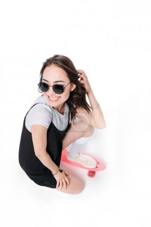 smiling woman in sunglasses sitting on skateboard