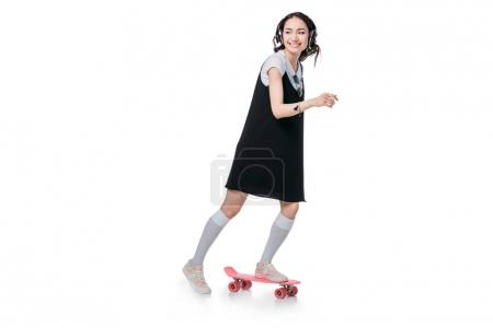 Photo for Asian girl listening music in headphones and riding on skateboard isolated on white - Royalty Free Image