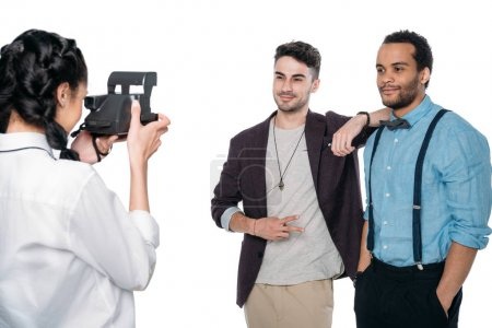 Photo for Girl taking photo of multiethnic friends with instant camera isolated on white - Royalty Free Image