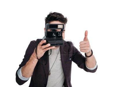man taking photo with polaroid camera