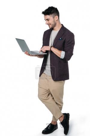 Foto de Hombre de Brunet en ropa casual escribiendo portátil aislado en blanco - Imagen libre de derechos
