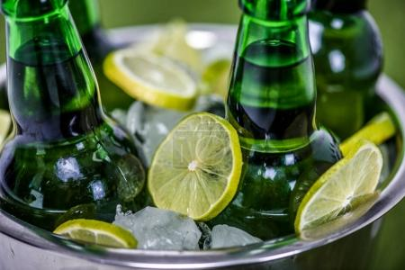 Photo for Closeup view of bucket with ice cubes, beer bottles and lemon slices - Royalty Free Image