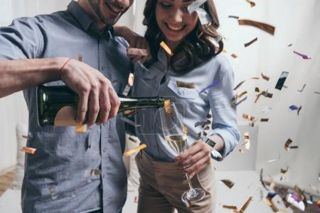 Photo for Cropped shot of smiling man pouring champagne to happy young woman at party - Royalty Free Image
