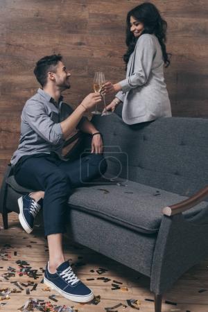 Photo pour Joyeux jeune couple assis sur le canapé et cliquetis avec des verres de champagne - image libre de droit