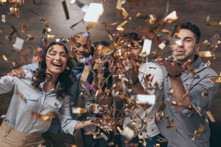 Photo pour Groupe multi-ethnique de joyeux jeunes rassemblés et célébrer avec des confettis - image libre de droit