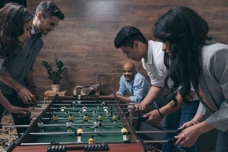 Friends playing foosball