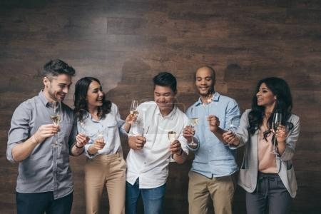 Photo for Cheerful young people holding glasses of champagne and burning sparklers indoors - Royalty Free Image