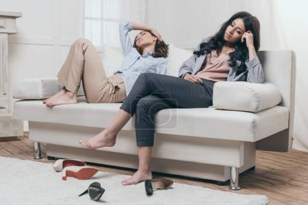 Tired women relaxing on sofa at home