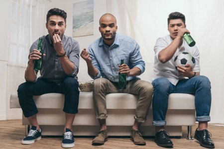 emotional friends watching football at home