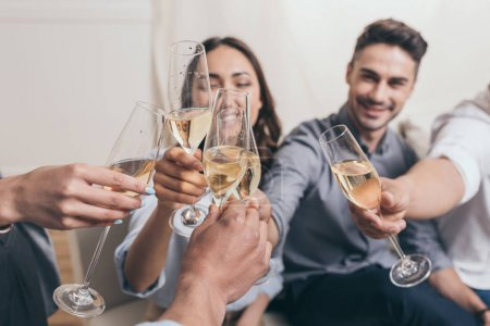 Photo for Young smiling friends clinking with champagne glasses while sitting at home - Royalty Free Image