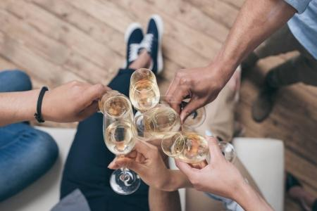 friends clinking with champagne glasses at home
