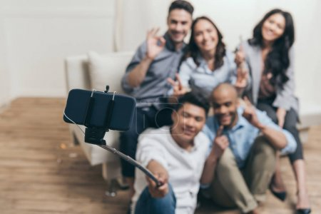 smiling multiethnic friends taking selfie
