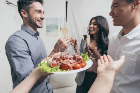 woman treating friends with snacks at party