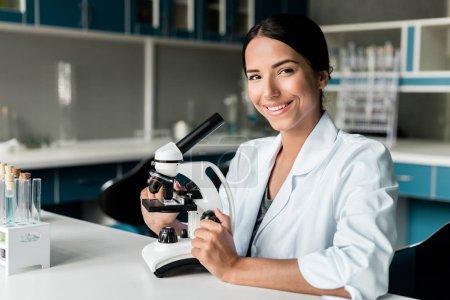 Photo pour Jeune chimiste séduisant en blouse blanche travaillant au microscope et souriant à la caméra en laboratoire - image libre de droit