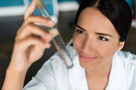 Photo pour Vue rapprochée d'un jeune scientifique souriant tenant une éprouvette en laboratoire chimique - image libre de droit