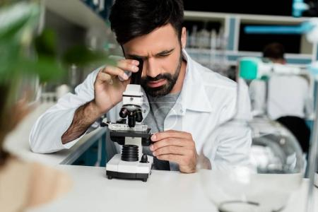 Photo for Focused male scientist in white coat working with microscope in chemical lab - Royalty Free Image
