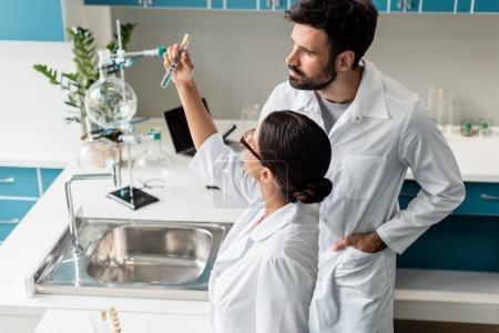Photo for Professional young chemists in white coats examining test tube with reagent in chemical lab - Royalty Free Image