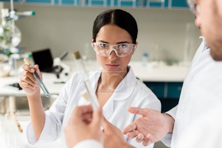 Photo for Young female scientist holding test tube with reagent and looking at camera in lab - Royalty Free Image