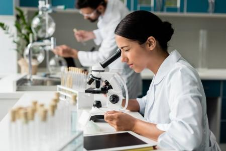 Photo for Concentrated young female scientist working with microscope in chemical lab - Royalty Free Image