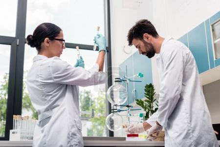Photo pour Jeunes chimistes professionnels en blouse blanche travaillant avec des flacons et éprouvettes en laboratoire chimique - image libre de droit
