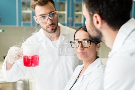 Photo for Team of professional young chemists wearing eyeglasses and lab coats making experiment - Royalty Free Image