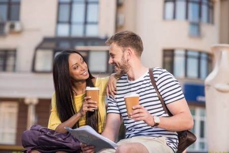Photo for Cheerful young multiethnic couple of tourists with map and disposable cups sitting in city - Royalty Free Image