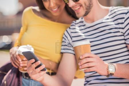 Photo pour Joyeux jeune couple multiethnique avec tasses à café en utilisant un smartphone en ville - image libre de droit