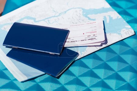 Photo for Close up of map, two passports and tickets lying on blue baggage - Royalty Free Image