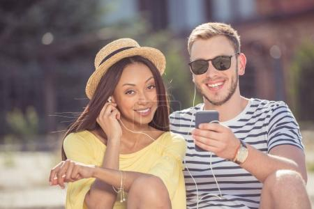 Photo for Young happy multiethnic couple smiling and listening music with earphones on smartphone - Royalty Free Image