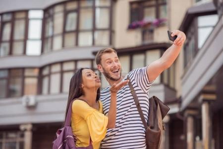 multiethnic couple taking selfie