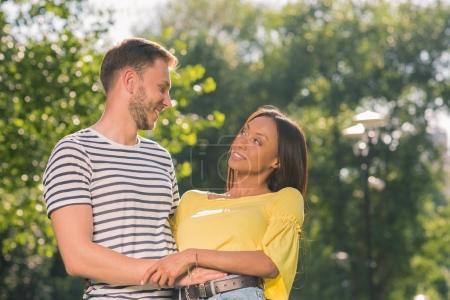 Photo pour Jeune couple multiethnique heureux embrassant dans le parc avec la lumière du soleil - image libre de droit