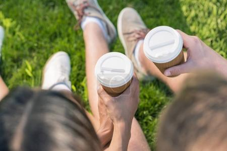 Photo for Couple drinking coffee from paper cups while sitting on grass - Royalty Free Image