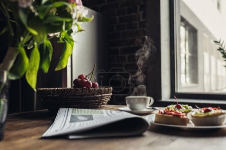 Photo for Still life of newspaper, breakfast with cakes and hot coffee on kitchen table in front of window - Royalty Free Image