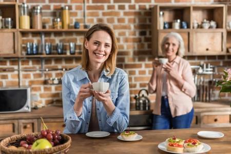 women having good time in kitchen