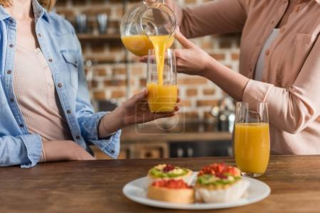 women drinking orange juice