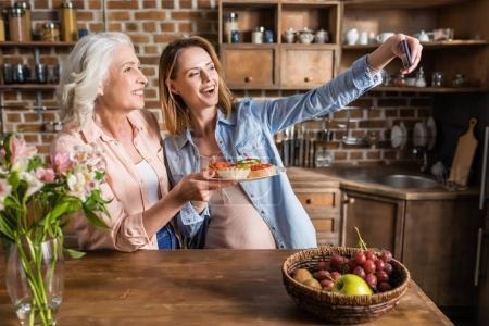 women taking selfie in kitchen