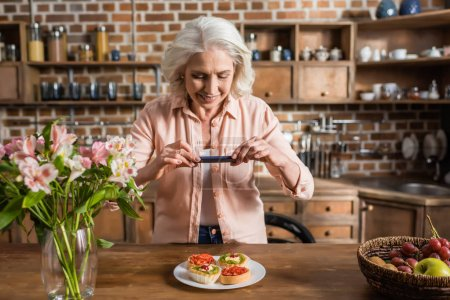 woman photographing plate with food at kitchen