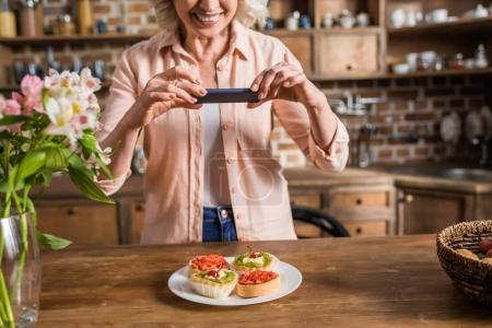 Photo for Portrait of senior woman photographing plate with food at kitchen - Royalty Free Image